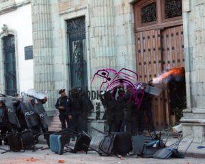 Porros universitarios se enfrentan y queman parte de inmueble historico